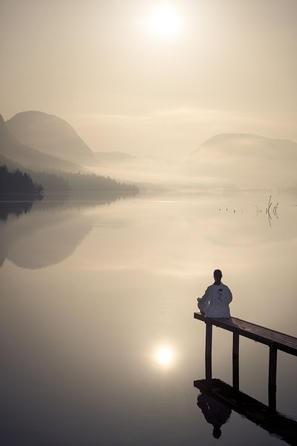 Meditant face au soleil levant